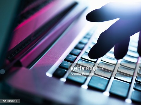 Close up of silhouetted male hand typing on laptop keyboard : Stockfoto