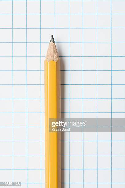 Close up of single yellow sharpened pencil on graph paper