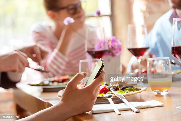 Close up of smart phone in hand during lunch