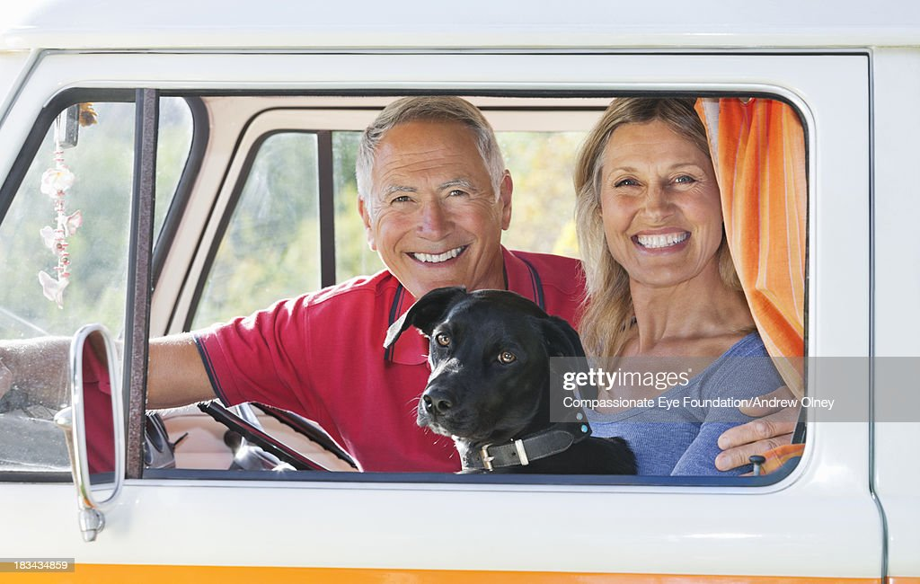 Close up of smiling couple in camper van with dog : Stock Photo