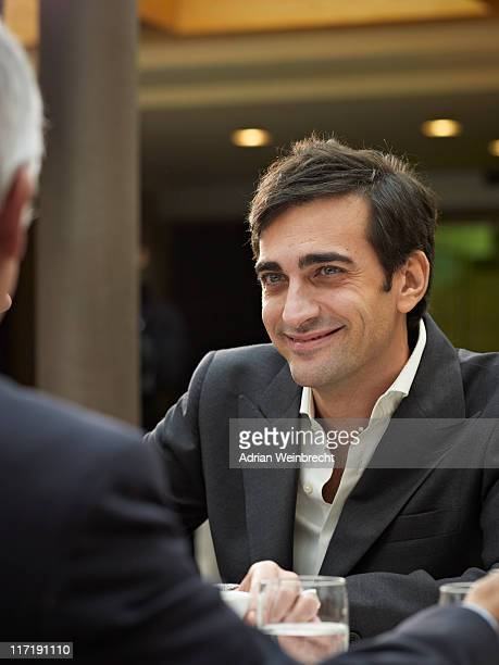 Close up of smiling man in a group meeting