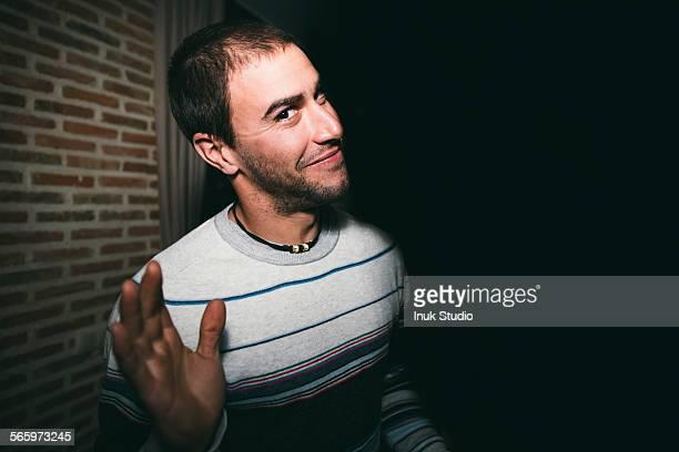 Close up of smiling man waving at night