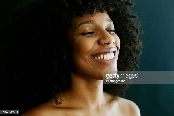Close up of smiling mixed race woman with eyes closed