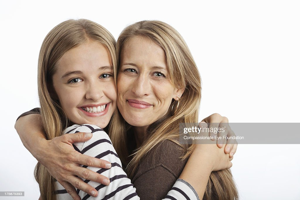 Close up of smiling mother and daughter hugging : Stock Photo