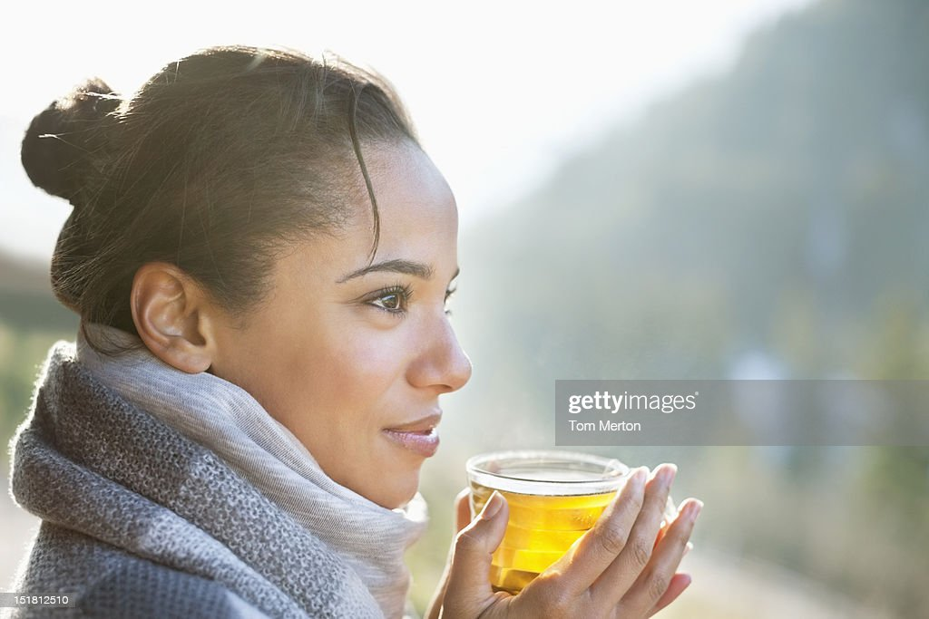 Close up of smiling woman drinking tea outdoors