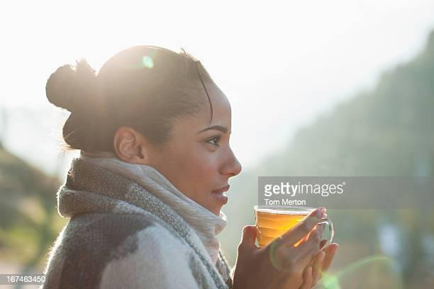 笑顔の女性のクローズアップの紅茶を飲みながら、屋外