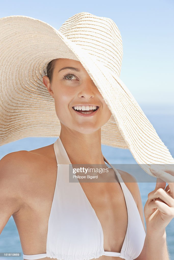 Close up of smiling woman in large sun hat on beach