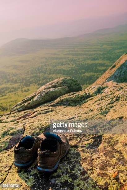 Close up of sneakers on rocky hilltop in remote landscape