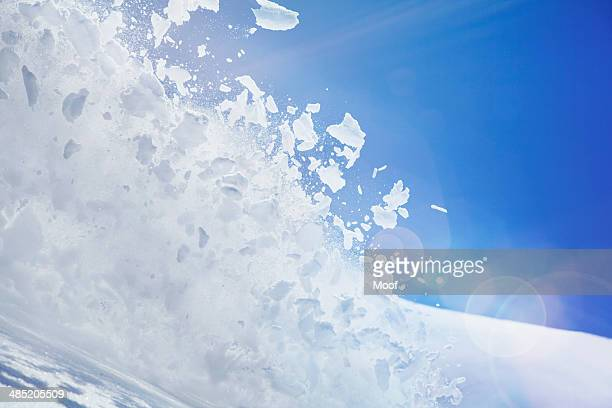 Close up of snow covered hill with powder snow and ice mid air