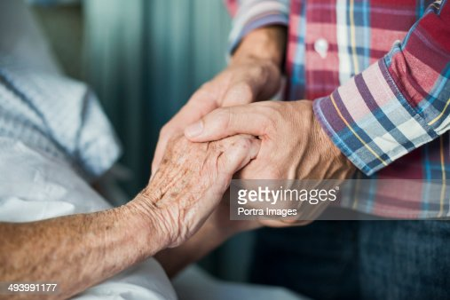 Close up of son holding his mothers hands