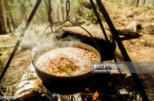 Close up of soup cooking over campfire