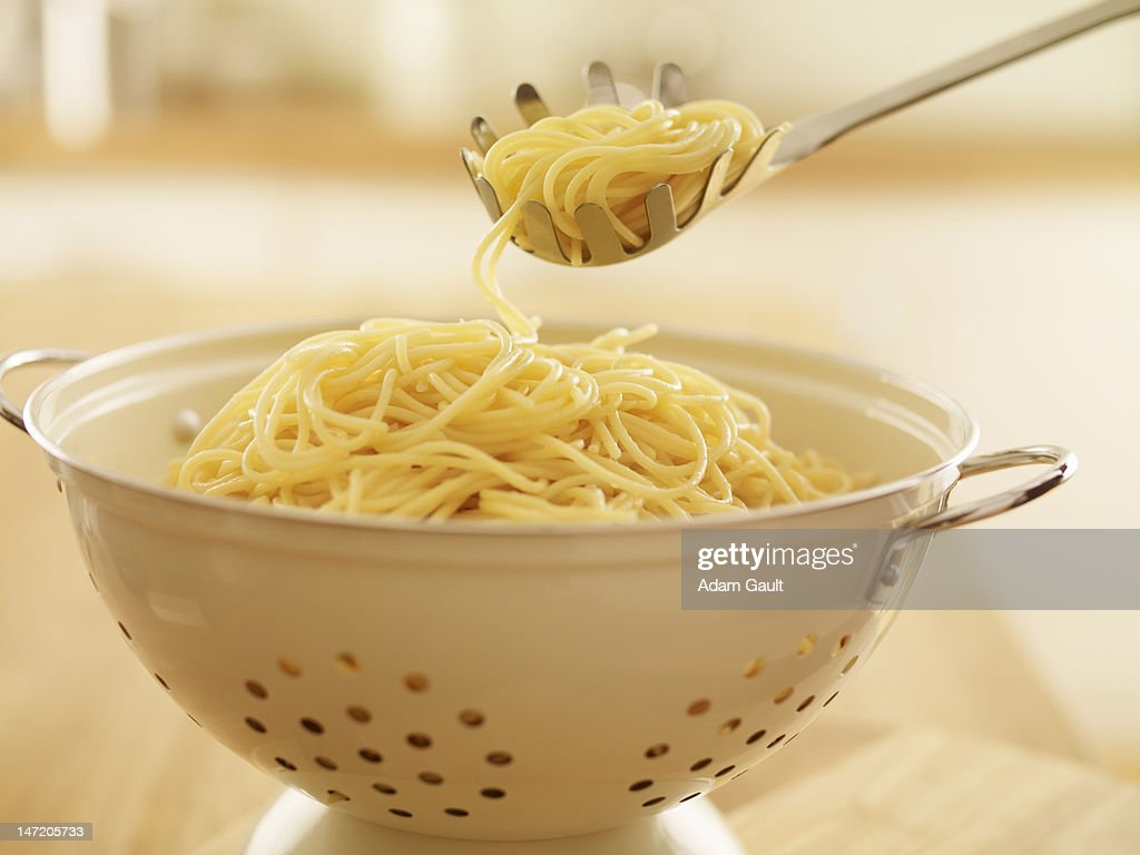 Close up of spoon scooping spaghetti in colander : Stock Photo
