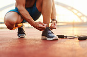 Close up of sporty man tying shoelace while kneeling in a court in the morning. Next to him skipping rope.