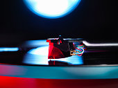 Close up of spot lit turntable and red stylus playing a vinyl record
