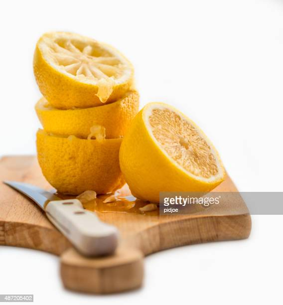 close up of  squeezed lemons  on wooden cutting board