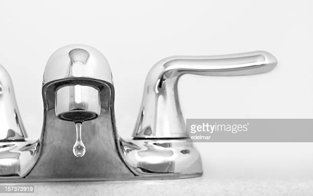 Close up of stainless steel faucet dripping water