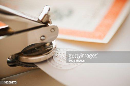 Close up of stamper making seal on paper