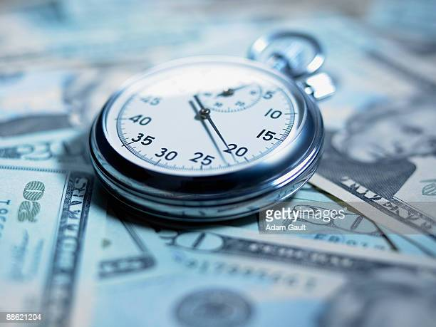 Close up of stopwatch on 20 dollar bills