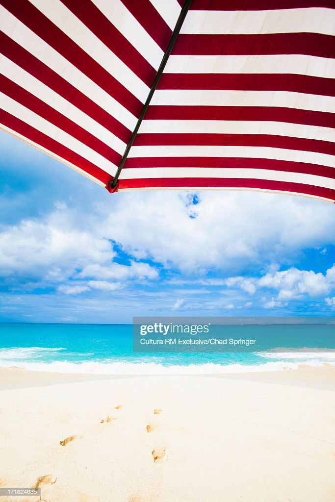 Close up of striped parasol in front of idyllic beach