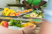 Unrecognizable African American male cafeteria worker serves healthy meal to student in line. Trays of bananas, apples, vegetables and salads are being served.