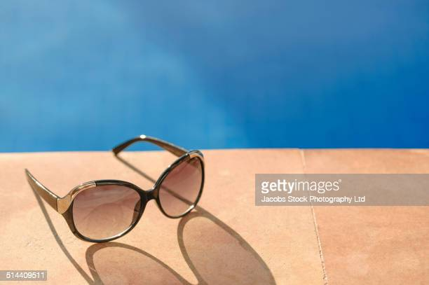 Close up of sunglasses by swimming pool