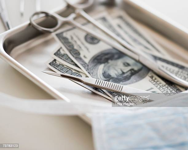 Close up of surgical tools and money