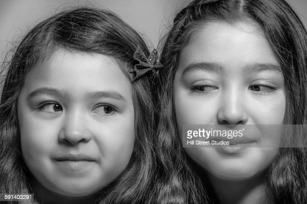 Close up of suspecting mixed race sisters