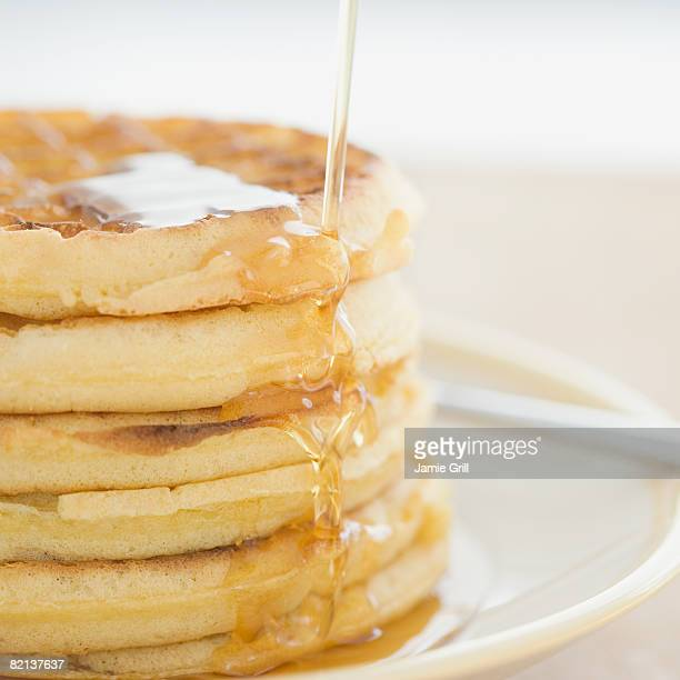 Close up of syrup pouring on waffles