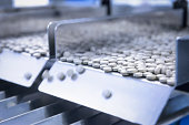 Close up of tablets in packing machine in pharmaceutical factory