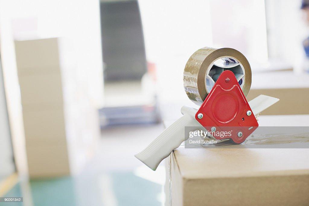 Close up of tape dispenser on cardboard box : Stock Photo