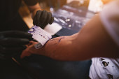 Close up of tattoo artists removing scetch sticker he previously made from customers arm.