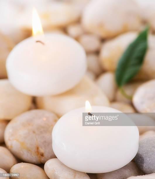 Close up of tea lights and green leaf on pebble stones, studio shot