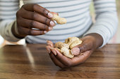 Close Up Of Teenage Girl With Handful Of Peanuts In Shells