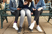 Close Up Of Teenage Girls With Mobile Phones In City Setting