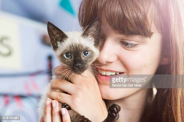 Close up of teenager holding kitten.