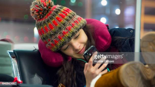 Close up of Teenager using cell phone and waiting for flight at the airport lounge