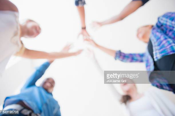 Close up of teenagers cheering with arms outstretched in huddle