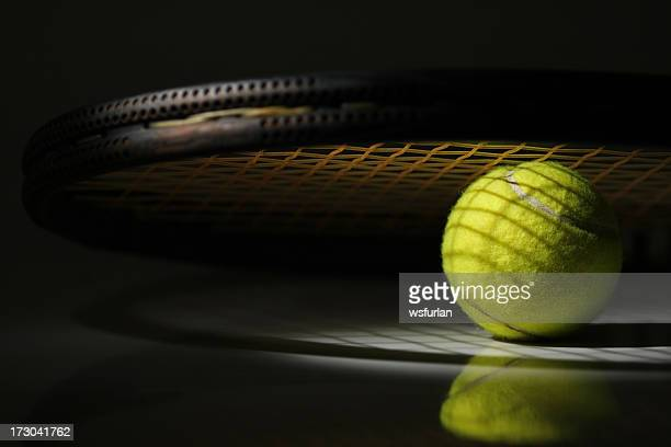 Close up of tennis ball under tennis racket with shadow