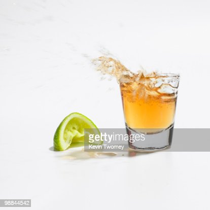 Close up of tequila splashing out of glass : Stock Photo