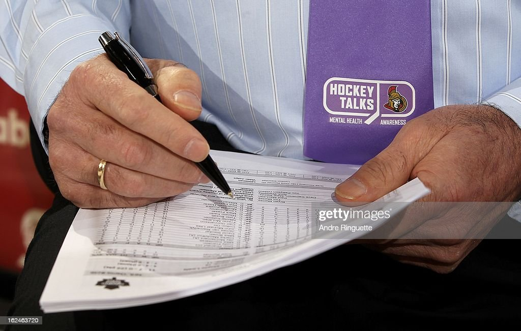 A close up of the purple tie and logo worn by head coach Paul MacLean of the Ottawa Senators on the Hockey Talks night, in support of Do It For Daron (D.I.F.D.), as he writes notes on the rosters during warmup prior to a game against theToronto Maple Leafs on February 23, 2013 at Scotiabank Place in Ottawa, Ontario, Canada.