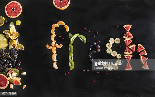 Close up of the word fresh written with sliced fruit