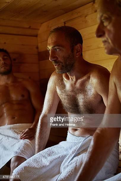 Close up of three men sitting in sauna
