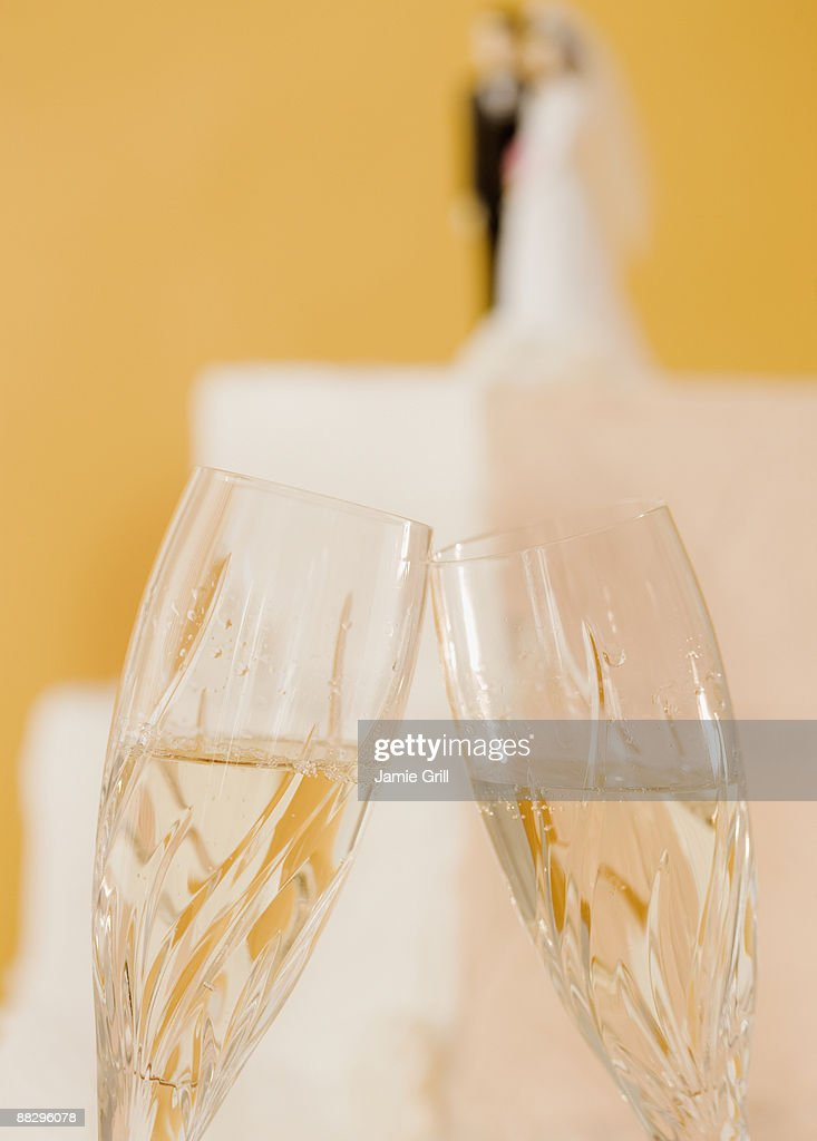 Close up of toasting champagne glasses and wedding cake : Stock Photo