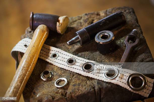 Close up of tools and eyelets in a sailmakers workshop.