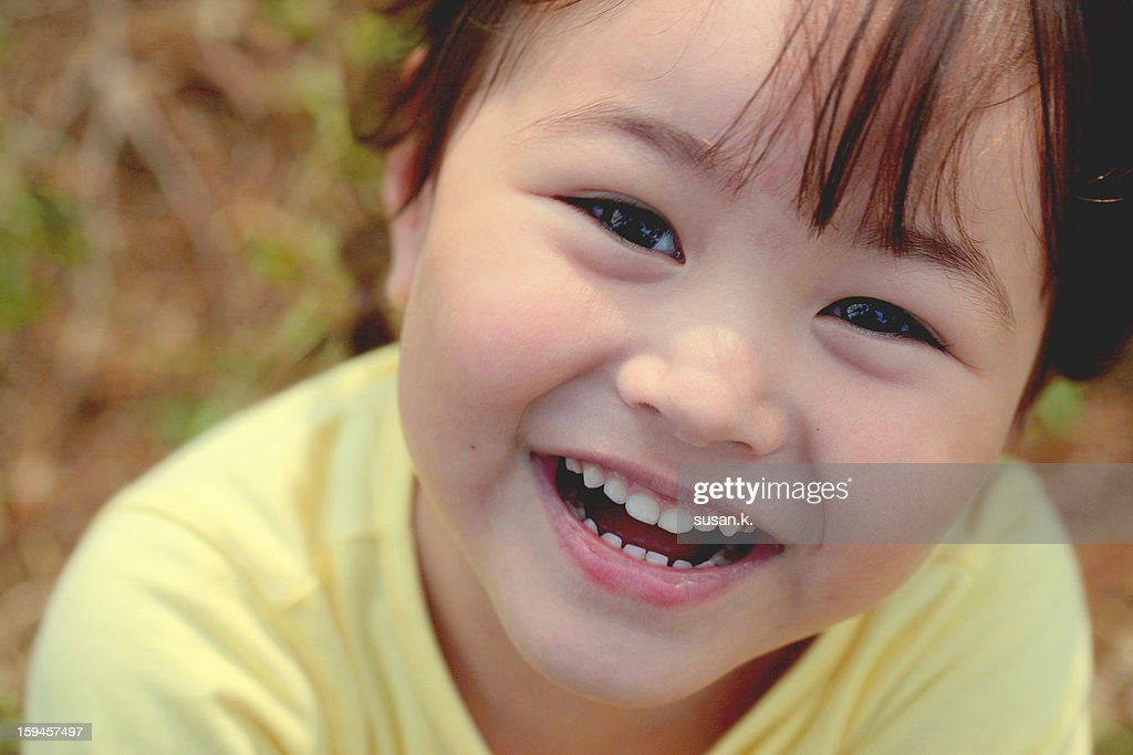 Close up of toothy smile little girl looking up. : Stock Photo
