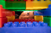 Close up of plastic blocks with child in the background. Boy peeking through construction on toy blocks.