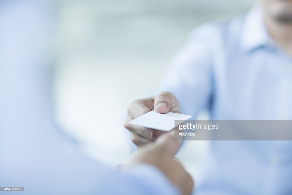 Close up of two businessmen exchanging business cards