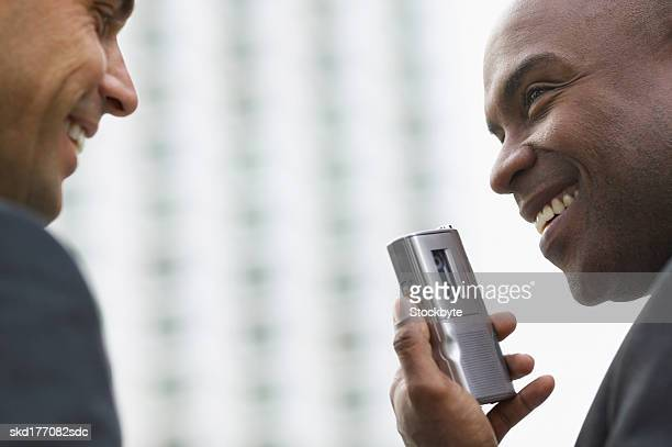 Close up of two businessmen talking and one of them holding a Dictaphone