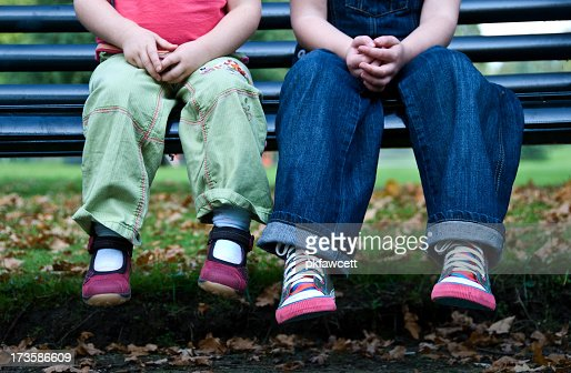 Close up of two children's legs on park bench outside
