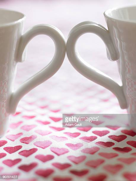 Close up of two coffee cups on table cloth decorated with hearts